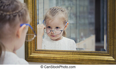 Little girl tries new glasses near mirror - shopping in ophthalmology clinic