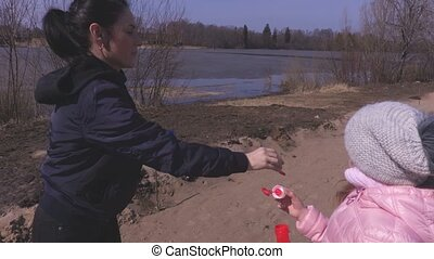 Little girl try to catch soap bubbles