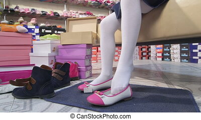 Little girl trying on new white pink flats in childrens shoe store