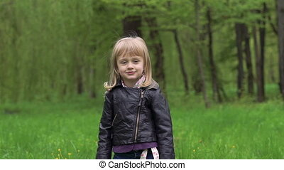 little girl turning aroung, touching her hair and smiling on a camera. Slowly