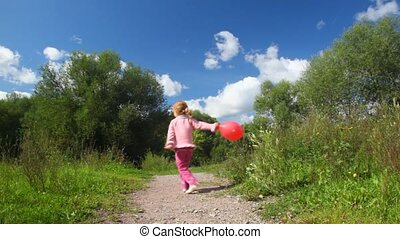 little girl turning round with red balloon in park