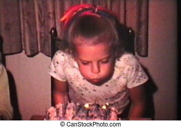 A cute little blond girl blows out the candles on her birthday cake as she celebrates turning ten years old. (SCANNED FROM 8mm FILM)