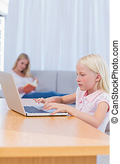 Little girl typing on laptop in the living room