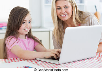 Little girl typing on laptop