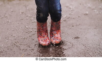 Little Girl Under Rain Jumping in a Puddle