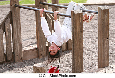 Little girl upside down at playground - Little girl hanging ...