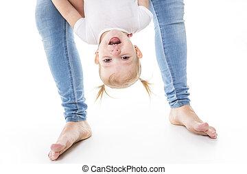 Little girl upside down on studio white background
