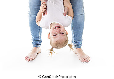 Little girl upside down on studio white background