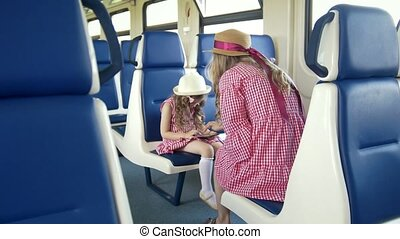 Little girl use a smartphone and sitting in front of her mom in the train