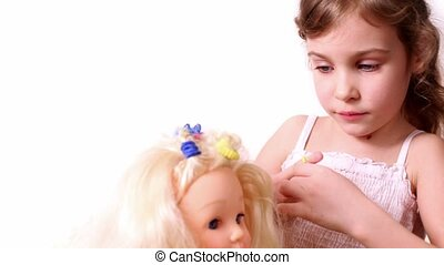 Little girl use elastic band to braid dolls hair, isolated