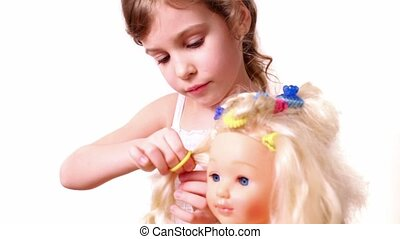 Little girl use elastic band to make dolls hairdo, isolated