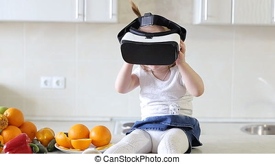 Little Girl Uses a Virtual Reality Glasses in The Kitchen.