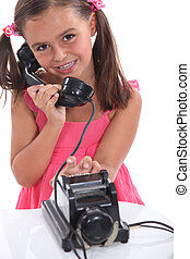 Little girl using an old fashioned telephone