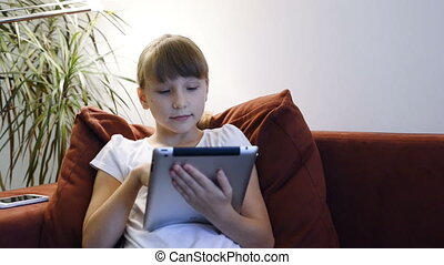 Little girl using digital tablet - Little girl sitting on...