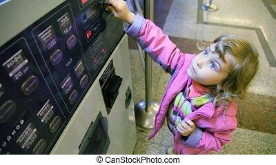 little girl using drinks dispenser indoor