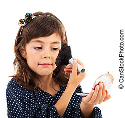 Little girl using face powder while looking in the mirror