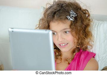 Little girl using her tablet computer