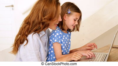 Little girl using laptop with her pretty mother at the table at home in living room