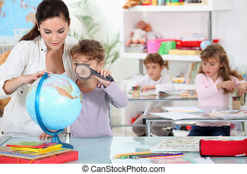 Little girl using magnifying glass on globe