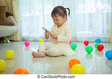 little girl using mobile phone - Happy little asian girl...