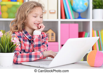 Little girl using modern laptop