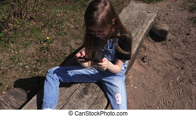 Little girl using smartphone at park on bench