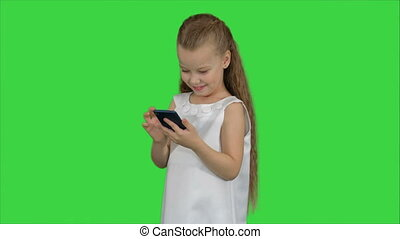 Little girl using smartphone on a Green Screen, Chroma Key....