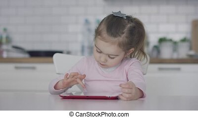 Little girl using tablet in kitchen