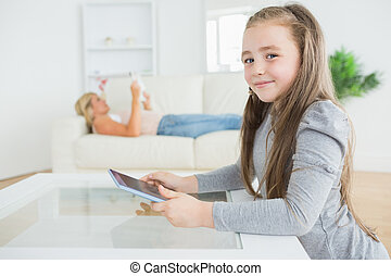 Little girl using tablet while moth