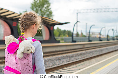 Little girl waiting for train at the railway station.