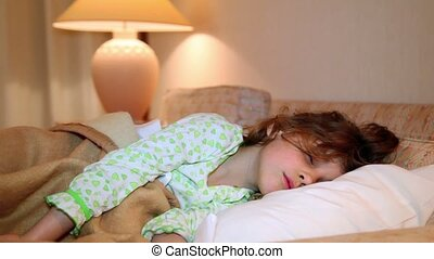Little girl wakes and smile in bed at background of lamp