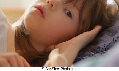 Little girl waking up in morning light