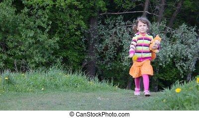 Little girl walk through the forest