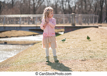 Little girl walking alone in the city park and enjoy.
