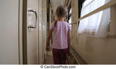 Little girl walking along an aisle in a train