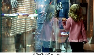 little girl walking along the museum display window with...