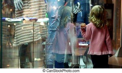 little girl walking along the museum display window