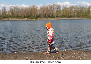 little girl walking along the riverbank