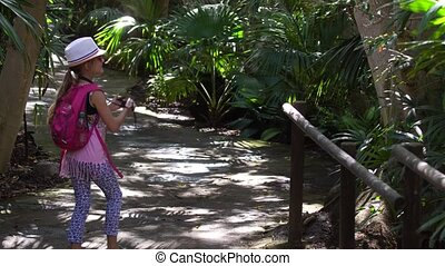 little girl walking and photographing in the park - cutegirl...