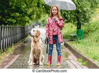Little girl walking dog in rainy park