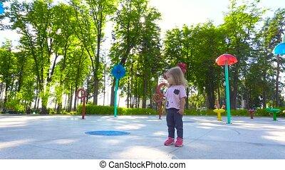 Little girl walking in amusement park - Little girl walking...