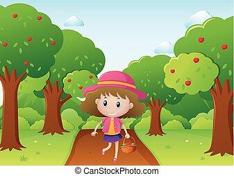 Little girl walking in apple orchard