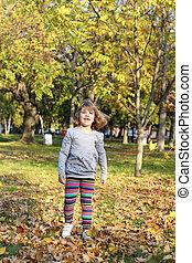 little girl walking in autumn park