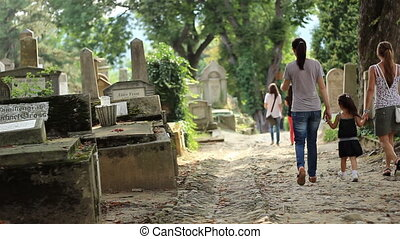 Little Girl Walking in Cemetery - A little girl accompanied...