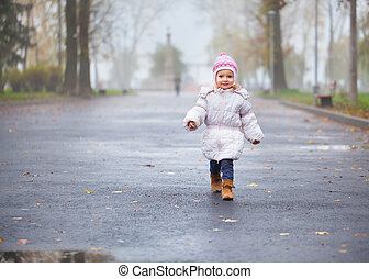 Little girl walking in the autumn park