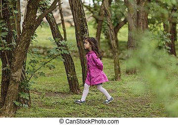 Little girl walking in the woods