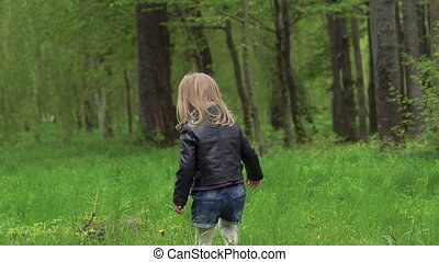 Little girl walking on a grass in the park. Slowly