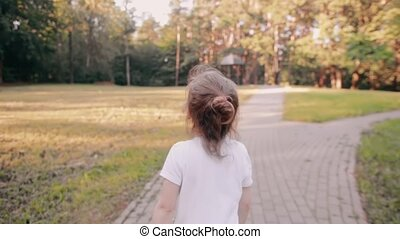 Little girl walking on a road in a park. A bun of fair hair has gold glow in the sun. Slow mo, back view