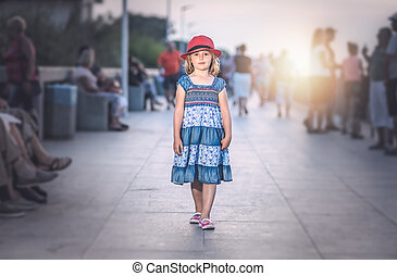 Little girl walking on a seaside promenade