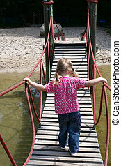 little girl walking on a suspended wooden bridge back view